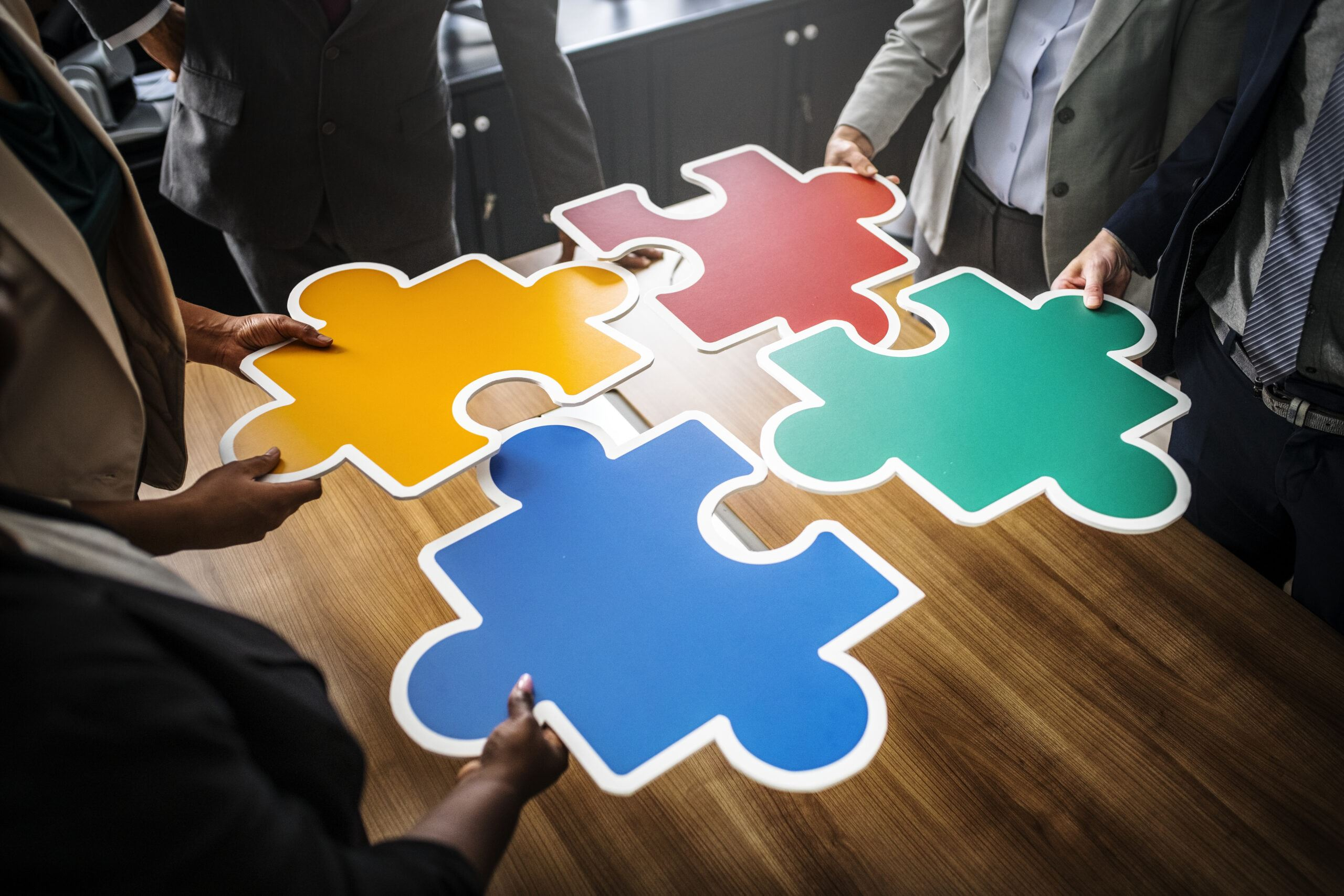 business men putting puzzle pieces together