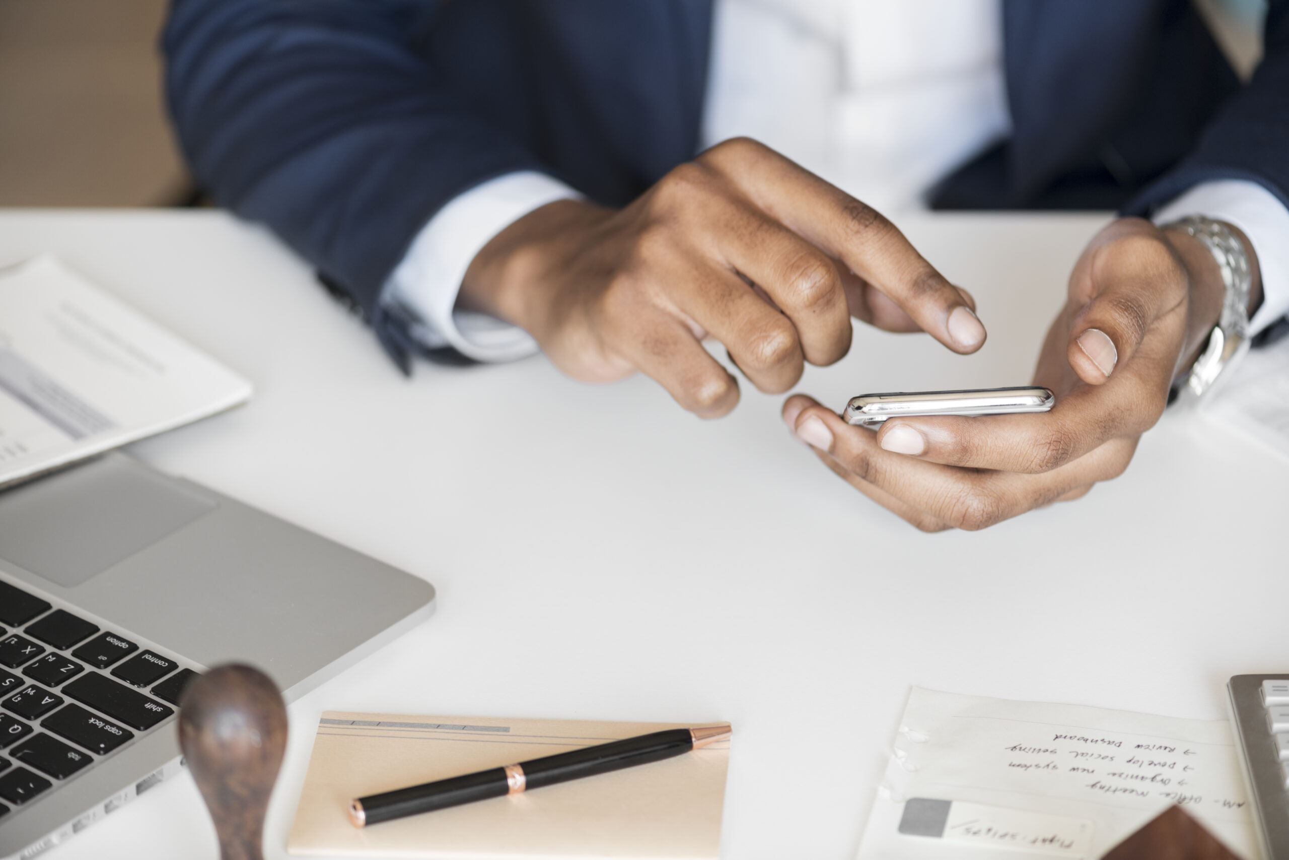 Man in suit at desk on phone