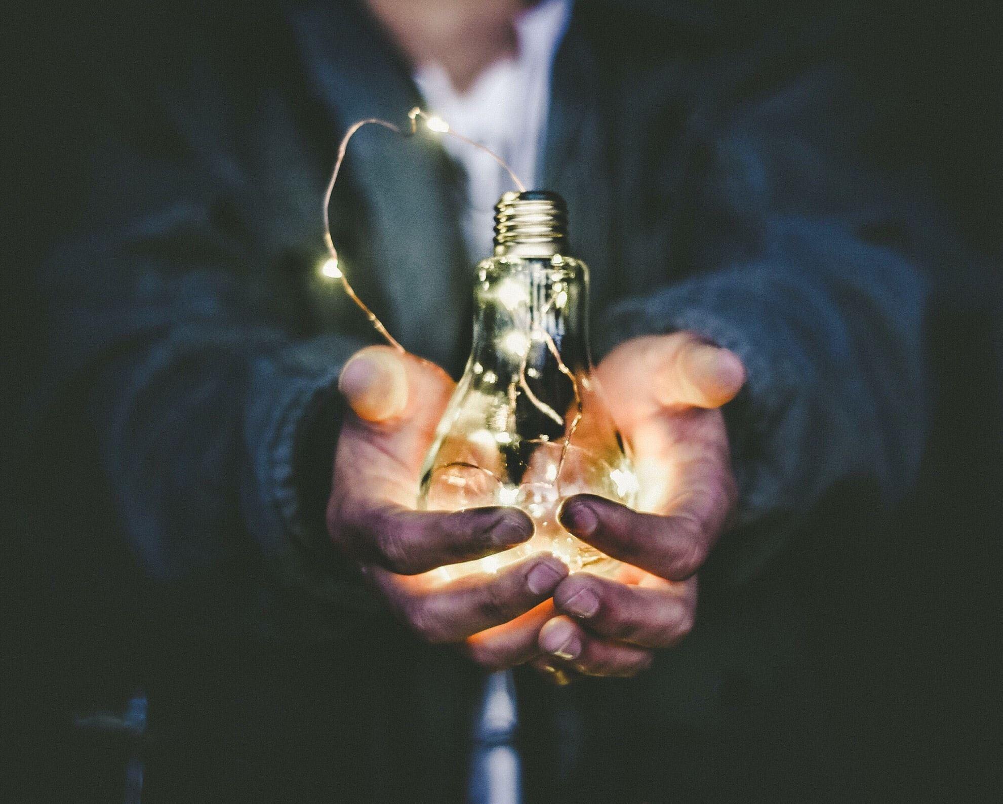 man holding lit up bulb